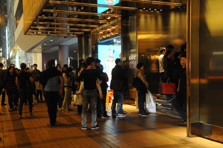 People waiting in line to enter high end stores.
