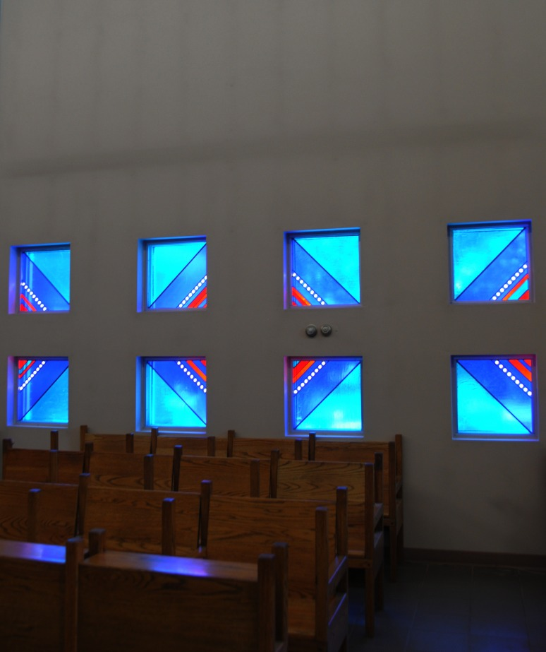 Pews surrounded by lovely stained glass windows.