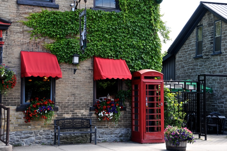 A bright red telephone booth livens up front of a shop on St. Lawrence Steet
